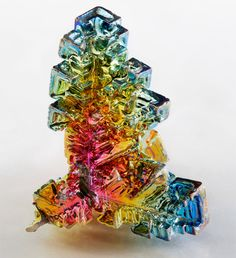 Bismuth is a brittle metal with a white, silver-pink hue, often occurring in its native form with an iridescent oxide tarnish showing many colors from yellow to blue. The spiral stair stepped structure of a bismuth crystal is the result of a higher growth rate around the outside edges than on the inside edges.