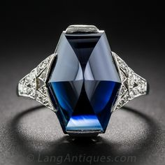 This striking French made ring, circa 1925, features a very special gemstone: a 7.25 carat sapphire fashioned into a faceted hexagonal buff-top cut. The dark midnight blue gemstone is presented in a gorgeous mounting, hand crafted in platinum with tiny single-cut and rose-cut diamonds glittering on each shoulder. The singular and sensational original Art Deco jewel measures just a tad shy of 5/8 inch. French hallmarks outside of the ring shank, numbered inside.