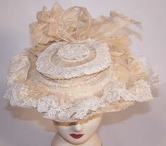 """""""This antique Victorian era Belle Epoque cream organdy wired ribbon white lace summer hat dates from 1890. It is made of an off white ecru cream color sheer organdy cotton fabric, with pleated gathering and white lace trim edging... Organdy ribbon bow trim on the back. The hat would have sat atop a full Gibson Girl style updo hairdo, secured with a hat pin. """" From 1860-1960."""