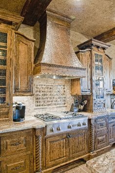 Warm wood, glass upper cabinets, hammered oven hood lends elegance & convenience