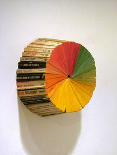 wow. seriously cool book art, I wonder if I could turn this into a functional clock with only the hour and minute hands and have the different colors at the 12, 3, 6 & 9 positions.  YES! it could work.