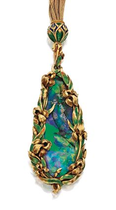 GOLD, OPAL AND ENAMEL SAUTOIR, MARCUS & CO. The drop-shaped black opal measuring approximately 16.0 by 5.1 mm, within a frame of gold irises accented by green enamel, extending to an openwork design of irises on the reverse, suspended from a multi-strand gold foxtail-link chain with a pendant element, slide bead and clasp decorated with blue and green enamel, length approximately 18 inches, signed M & Co.; circa 1900.