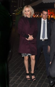 In a maroon Burberry trench coat while stepping out in London.    - ELLE.com