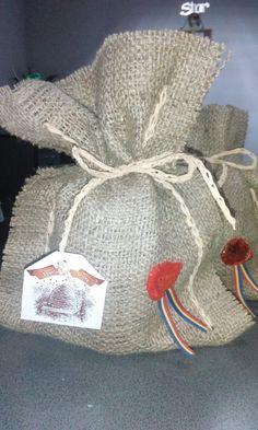 Saculet din panza de sac cusut cu rafie naturală, continând un borcan cu miere.