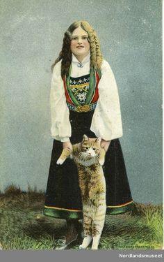 Postkort med bilde av jente i Vossabunad (hvit skjorte, sort stakk, rød vest med grønne bånd og perlebringklut). som holder en katt i armene. Katten står med bakføttene i bakken strukket oppover. Gress. Bakside: Rødt postfrimerke, posthorn, 3øre. Stemplet Bjarkø desember 1910. Kitty Cats, Norway, Scandinavian, Princess Zelda, Embroidery, Beauty, Kittens, Needlepoint