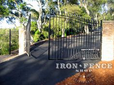 An arched wrought iron driveway gate with an automatic opener system can make for a beautiful and convenient entryway to your home