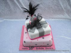 Parcel Cake. Two tier stacked square parcel cake the lower tier covered in pink with black and pink stars and the upper tier decorated with a large chiffon ribbon. Topped with a hot pink and black feathered wired explosion and glitter 16
