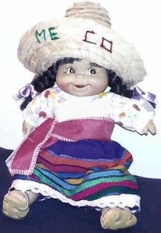 Searching – MEXICAN DOLL with BLACK PIGTAILS Wearing PRINT & STRIPE DRESS, SASH, SANDALS, SOMBRERO Printed MEXICO