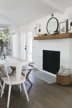 Modern farmhouse dining room. Bright room with white walls and nice fireplace