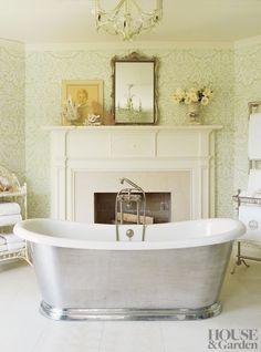 A traditional bathroom by Annie Selke features a working fireplace.