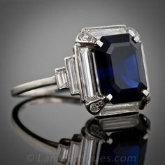 Actually, it weighs 4.96 cts. - but what's a few points among friends? This magnificent, rich velvety blue emerald cut sapphire is surrounded by elegant, extra long baguette diamonds which taper and step down the shoulders in classic Art Deco style. Each prong is dotted with an additional sparkling round cut diamond. Circa 1930; a breathtaking sapphire and diamond ring! Platinum, of course,