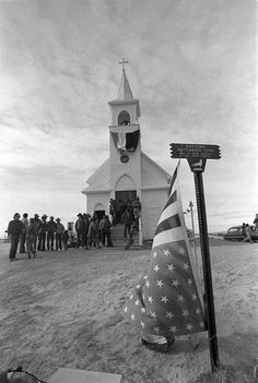 A U.S. flag flies upside down March 3, 1973 outside a church occupied by members of the American Indian Movement (AIM), background, on the site of the 1890 massacre at Wounded Knee, S.D.. AIM's occupation of Wounded Knee triggered a violent standoff with federal authorities. (AP Photo/Jim Mone) Rapid City Journal