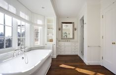 Absolutely beautiful bathroom features freestanding bathtub paired with floor mounted tub filler filling bay window flanked by built-in cabinets with glass doors adorned with towel holders.