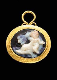 A ROMAN GOLD AND ONYX CAMEO PENDANT, circa 2nd Century A.D. The plain oval box-bezel with a projecting rim and a suspension loop above formed from wire with voluted end, the bezel set with an onyx cameo with a white layer against a brown ground, carved in high relief with a boy riding a dolphin upon the waves, the boy seated on the dolphin's back, grasping its forward-curving tail in his right hand, the boy's head carved in a pale pink layer of the stone.