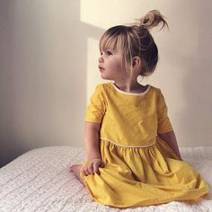 adorable girl in yellow dress and messy bun