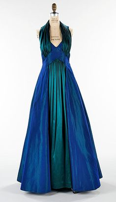 "1936 ""Styx"" gown: Hawes created simple bias-cut comfortable garments with deep armholes and natural shoulders that would be worn with flat-soled shoes. The striking combination of blue/green changeante taffeta and green satin reflect Hawes' interest in surface treatment and design."