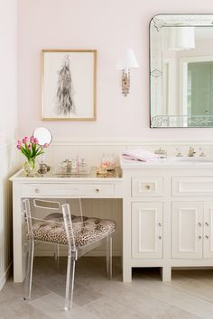 Stunning bathroom features pink paint on upper walls and ivory beadboard trim on lower walls lined with an ivory make-up vanity with mirrored top under a framed haute couture fashion sketch. Find more #bathroom #inspiration via @BainUltra.