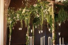 Structural materials: birch trunks, curly willow, honey locust branches, and smilax vine wound down around birch trunks with accents of candles