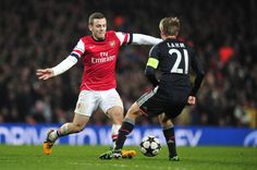 Arsenal's English midfielder Jack Wilshere (L) nutmegs Bayern Munich's German defender Philipp Lahm (R) during the UEFA Champions League round of 16 football match between Arsenal and Bayern Munich at the Emirates Stadium in north London on February 19, 2013. Bayern Munich won 3-1