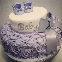 Lilac or lavender baby shower cake for girl. Baby shoes, bow, and roses. Top tier in fondant, bottom tier is buttercream and shoes and bow in gumpaste.