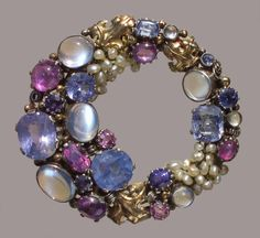DORRIE NOSSITER,  Brooch,  Silver, Gold, Moonstone, Sapphire, Ruby, Seed Pearl,  H: 5.3 cm (2.09 in)  W: 5 cm (1.97 in)   British, c.1930,  Fitted Case,  Open circular form, with wire- scrolls & leaves.