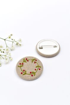 Handmade embroidered holly wreath pin badge.  This simple but elegant holly wreath pin brooch is made from natural linen fabric.  The wreath and red berries are all delicately hand sewn.  These little sewn badges look great pinned onto clothing or accessories.  A lovely little gift, ideal for the festive season or as a Christmas stocking filler. #embroideredholly #hollybadge #hollybrooch #christmasbadge #festivebrooch #embroideredhollywreath #embroideredbadge #hollypin #hollypinbadge Floral Print Fabric, Floral Prints, Holly Wreath, Liberty Of London Fabric, Christmas Stocking Fillers, Red Berries, Vintage Fabrics, Pin Badges, Natural Linen