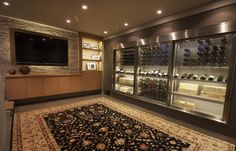 Basement entertainment room with climate controlled built-in wine cabinet wine cellar containing the Cable Wine System.
