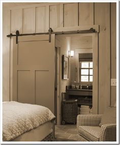 Love the white wood paneling and the sliding barn door to the bathroom.