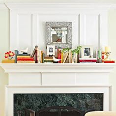 Use books as graphic, colorful pedestals to give framed photos and other treasured objects a lift. Alternating horizontal and vertical stacks of books add interest to this mantel. Try the same idea on any shelf or down the center of a table.