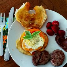 Yummy breakfast- sausage, strawberries, nutella, croissant, and egg bordered by pepper and garnished with basil.