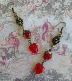 Red Hot Heart Earrings .. Made with Red Glass beads and hearts and brass caps and connectors .. Designed By Jann Tague .. Clever Designs .. https://www.facebook.com/#!/JewelsByJann