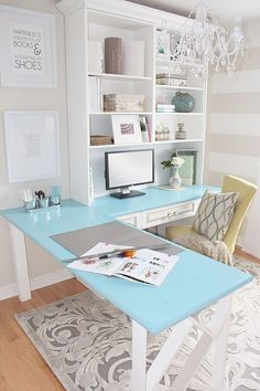 Home office with light blue desk, plush chair, decorative rug, chandelier, and striped wall decor with built-in shelves