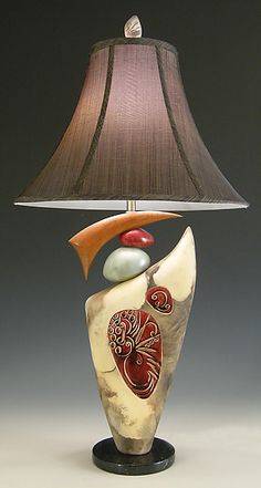 Created by Jan Jacque    A unique sculptural ceramic lamp created by Jan Jacque combines both clay and cherry wood elements. The beautifully crafted clay pieces are artfully stacked atop a marble base. The silk shade is black/gold.