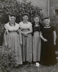 Vier vrouwen uit Westkapelle in Walcherse streekdracht. De tweede vrouw van links draagt daagse dracht, de overige drie vrouwen zijn gekleed in kerkdracht. De twee vrouwen rechts zijn in de rouw. 1956 #Zeeland #Walcheren