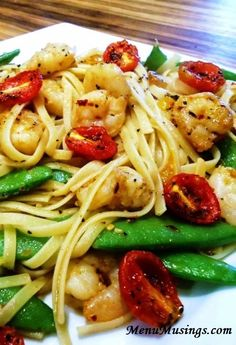 Spicy Garlic Shrimp - medium to large shrimp - extra virgin olive oil - butter - white wine or chicken broth - 5 garlic cloves - red and yellow bell peppers - crushed red pepper flakes - Montreal  seasoning - large lemon - grape tomatoes - fresh sugar snap peas or fresh green beans or fresh asparagus - linguini