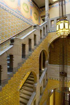Bovenin het trappenhuis van de Burcht met rechts een lamp van Jan Eisenloeffel en links wandschilderingen van H.P. Berlage. Foto Arjan Bronkhorst