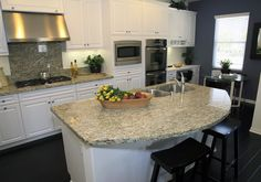 Curved+granite+kitchen+island+with+undercounter+sink Crown moulding on cabinets