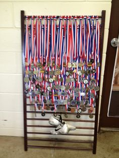My niece's track medals displayed on a repurposed crib side.
