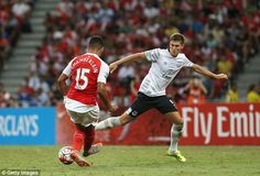 Everton defender John Stones (right) tries to close down Arsenal wingerAlex Oxlade-Chambe...