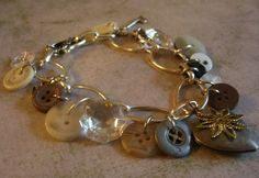 """A lovely mix of vintage buttons, upcycled chandelier crystals, a heart shaped locket, an tisy bitsy key, and a tiny silver plated dove make up this unique bracelet. Perfect addition to any outfit! Will fit up to an 8.5"""" wrist. SOLD"""