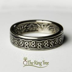 This is an extremely attractive ring with a beautiful finish! This ring will look great on you, or make a perfect gift for that special someone!    This coin ring was hand crafted and hand polished from a Suriname 100 cent coin. It features an antique finish with polished raised details, which give it an extremely stunning appearance. It has a beautiful knot design around the outside of the band…