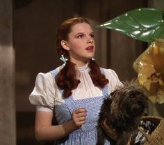 Our Favorite Wizard of Oz Looks of All Time: Judy Garland as Dorothy in The Wizard of Oz, 1939  This outfit from the original film is pretty much what comes to mind when we think of The Wizard of Oz. From the sweet curly pigtails to the blue gingham dress to--of course--the ruby red slippers, this outfit is so memorable it's a common Halloween costume. Can't get much more iconic than that.