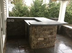 A custom natural stone service bar with polished bluestone countertops.