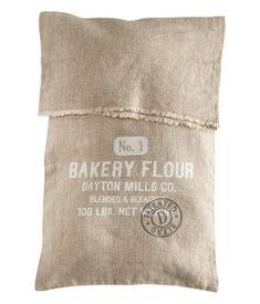 Een kussenhoes van gewassen linnen met geprint motief. Opening met onafgewerkte randen.