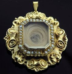 Victorian mourning pendant is made with 18k yellow gold, seed pearls, and a coiled lock of hair behind a glass panel.