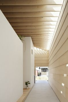 outdoor hallway with white wall and wooden wall, beams ceiling, skylight and white floor  - wood cladding looks like G1S plywood?...very cool!