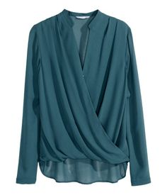Blouse in airy chiffon with wrapover draping at front. Button at front and long sleeves with buttons at cuffs. Slightly longer at back.(Drapped blouse in teal)