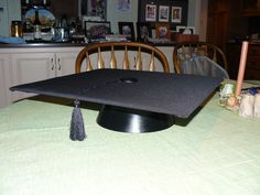Motar Board Cake Stand. I used foam board covered with black polyesther. The cap was a bowl from the dollar store spray painted black and inverted. I glued a button and tassel on it and we used cupcakes on it. Sooo cute and easy!