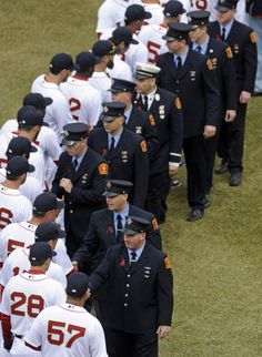 Members of the Boston Red Sox honor members of the Boston Fire Department prior to the Boston Red Sox home opener against the Milwaukee Brewers at Fenway Park on Friday, April 4, 2014.