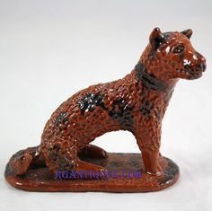 Pennsylvania redware dog with a manganese and lead glaze. 4,25 inches tall.